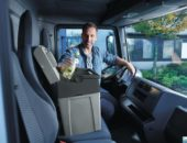 Дальнобойщик кладет продукты в автомобильный мини-холодильник