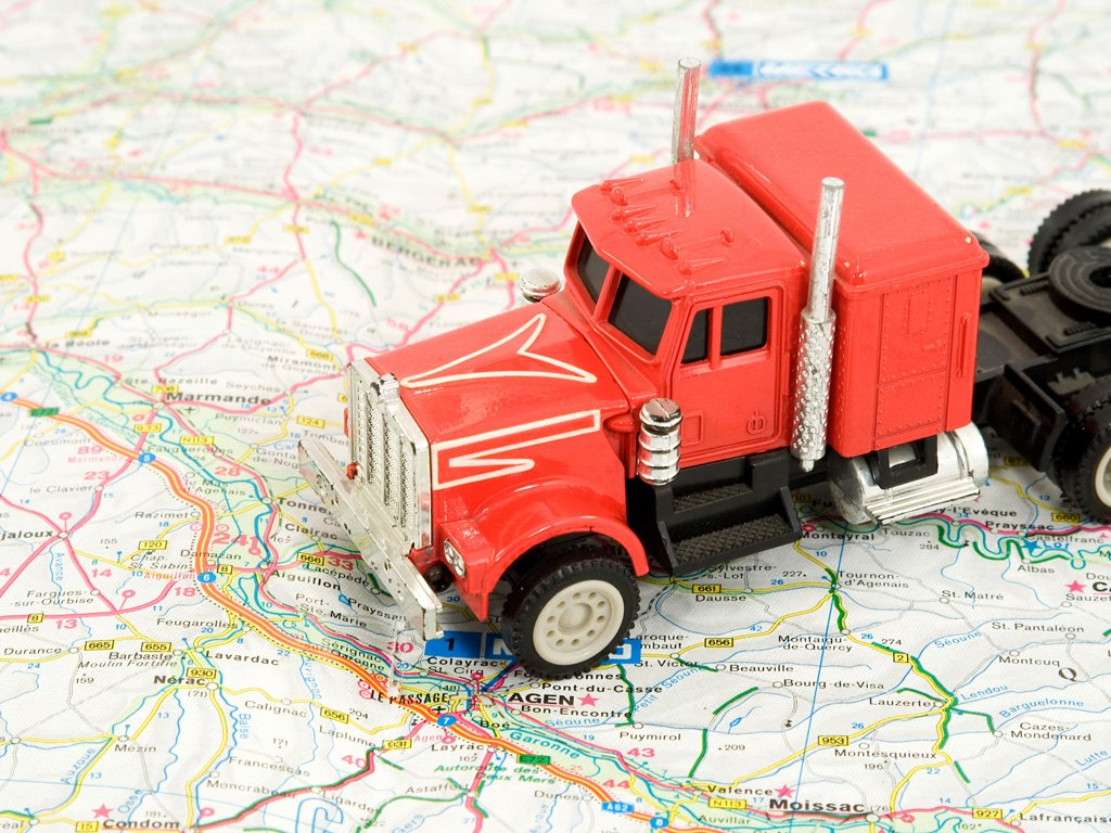 transportation and travel concept - truck on the map